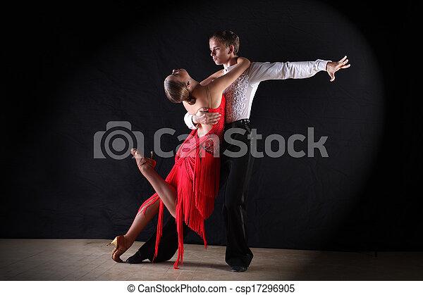 Latino dancers in ballroom against on black - csp17296905