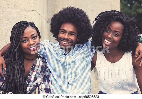 Laughing african american hipster man with two beautiful woman - csp60505523