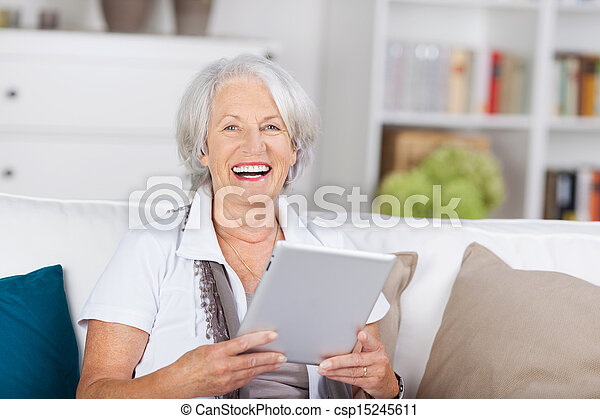 Laughing beautiful senior with a tablet-pc - csp15245611