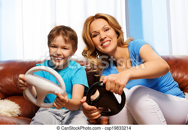 Laughing son and mom driving steering wheels - csp19833214