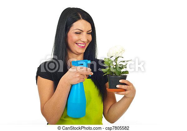Laughing woman spraying flower in pot - csp7805582