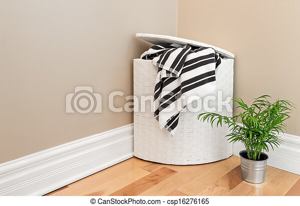 Laundry basket and plant in the room corner - csp16276165