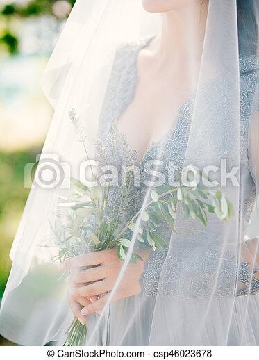 Lavender Wedding bouquet in hands of the bride under veil in pal - csp46023678