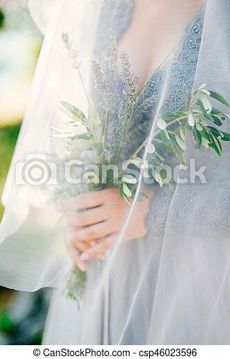 Lavender Wedding bouquet in hands of the bride under veil in pal - csp46023596