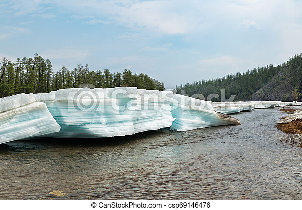 Layered turquoise lumps of ice on the river - csp69146476