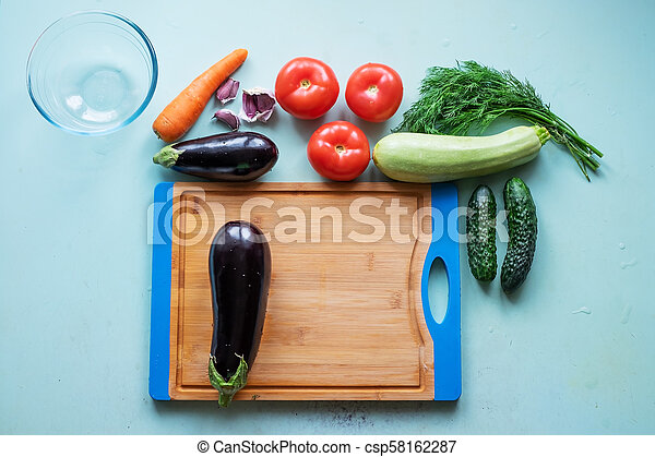 Layout of whole and sliced eggplants, cutting board and other fresh vegetables. - csp58162287