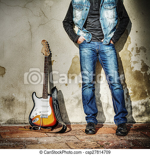 leaning on the wall with an electric guitar - csp27814709
