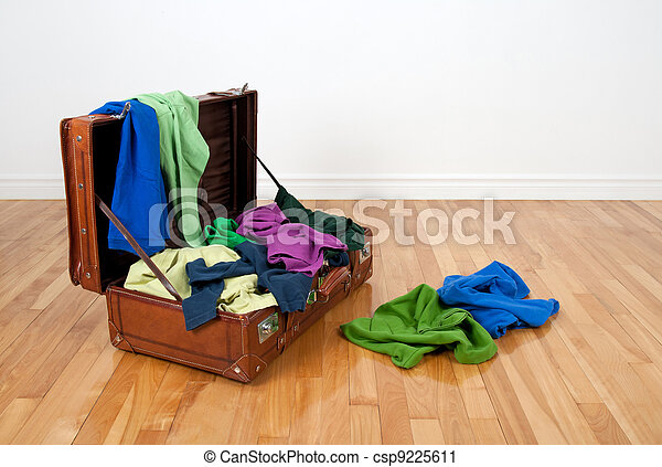 Leather suitcase full of colorful clothing - csp9225611