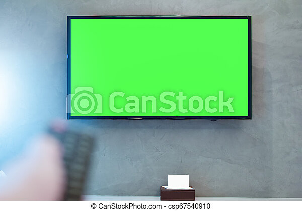 LED screen TV with green screen compositing. TV or television - green screen on the wall in modern room with blurred hand on remote - csp67540910