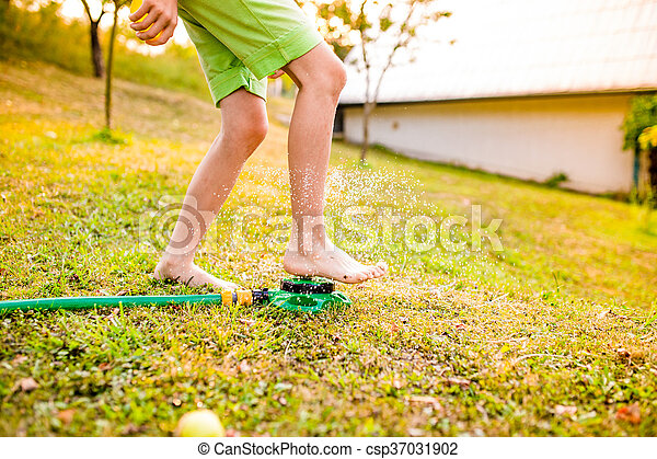 Legs of a boy in garden at the sprinkler - csp37031902