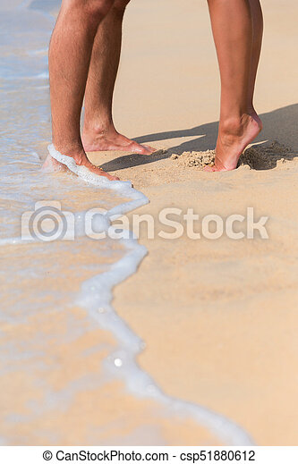 Legs of a kissing couple in love on a sea beach
