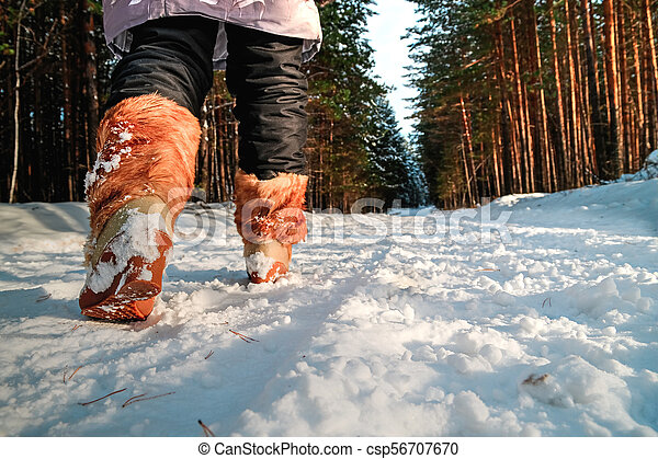 Legs of a woman in warm boots on the snow. - csp56707670