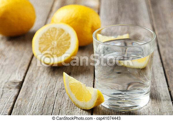 Lemons with glass of water on grey wooden background - csp41074443