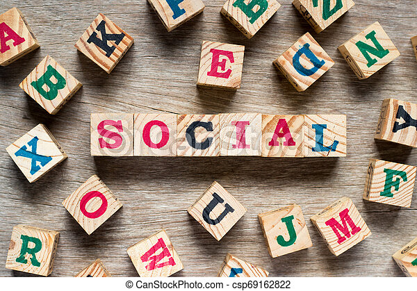 Letter block in word social with another alphabet on wood background - csp69162822