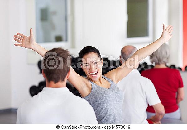 Mujer con brazos levantados sentada con grupo en el gimnasio - csp14573019
