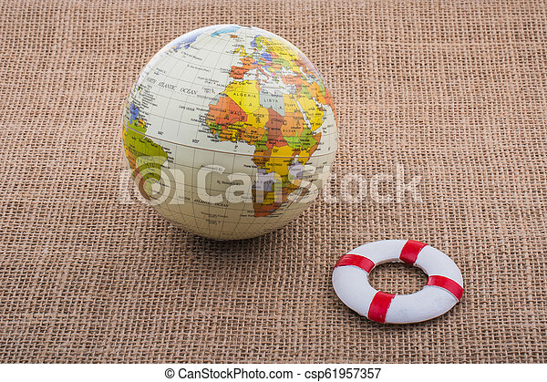 Life preserver beside a globe on canvas - csp61957357
