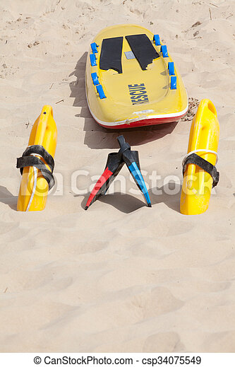 Lifesaving raft, floatation devices and swimming fins on beach - csp34075549