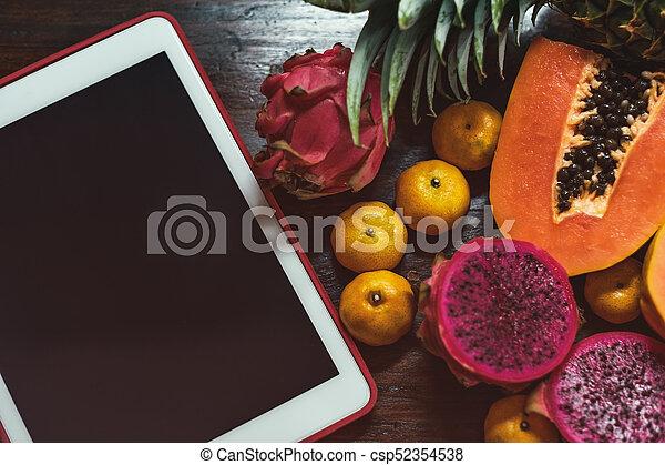 Tropisches Obst nahe modernem Laptop auf Holzhintergrund. Veganischer Lebensstil. - csp52354538