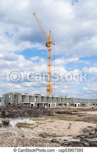 Lift crane building a new residential building on blue sky and white clouds. - csp53907393