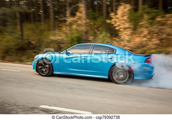 Light blue sport sedan on the road - csp79392738