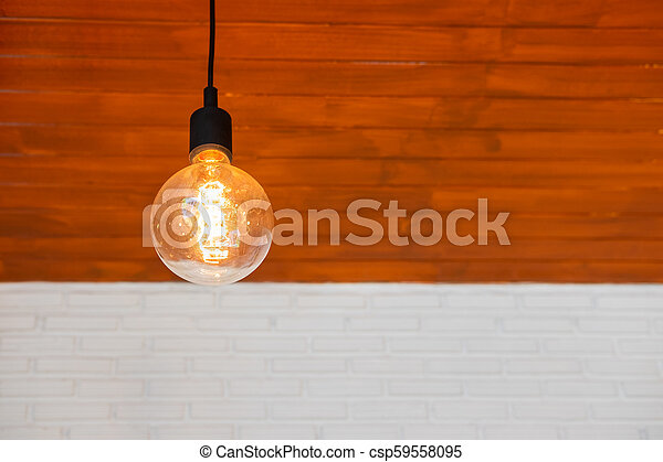 Light bulb on wood and white brick wall - csp59558095