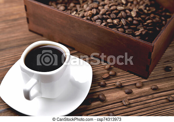light coffee beans wooden box with coffee, natural wooden background - csp74313973