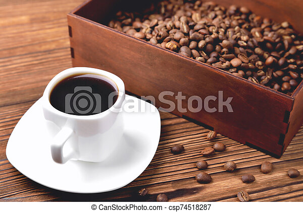 light coffee beans wooden box with coffee, natural wooden background - csp74518287