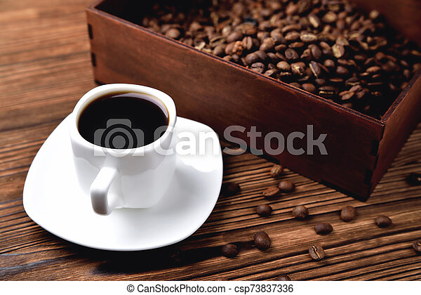 light coffee beans wooden box with coffee, natural wooden background - csp73837336