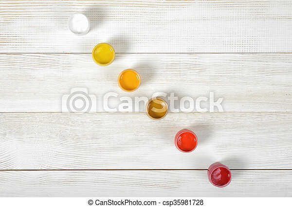 Light colors of gouache jars are diagonally on white background in top view - csp35981728