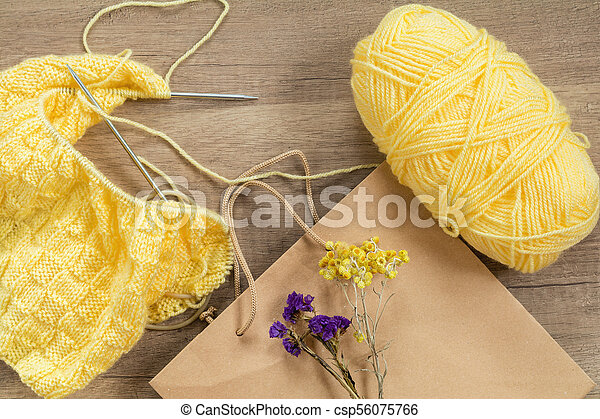 Light yellow knitting wool and knitting needles on wooden background - csp56075766