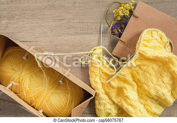 Light yellow knitting wool and knitting needles on wooden background - csp56075767