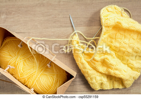 Light yellow knitting wool and knitting needles on wooden background - csp55291159