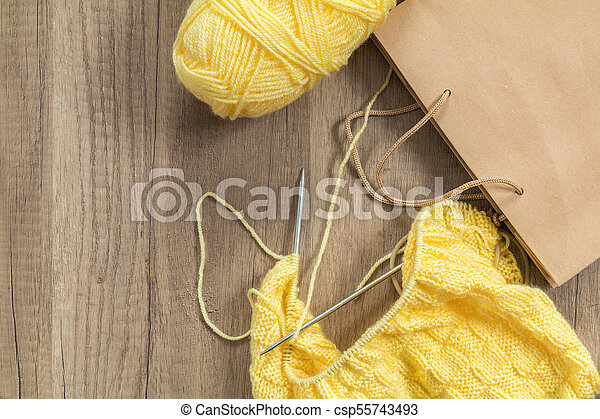 Light yellow knitting wool and knitting needles on wooden background - csp55743493