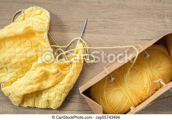 Light yellow knitting wool and knitting needles on wooden background - csp55743494
