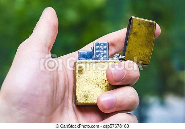 lighter of gold color in hand against the background of nature - csp57678163