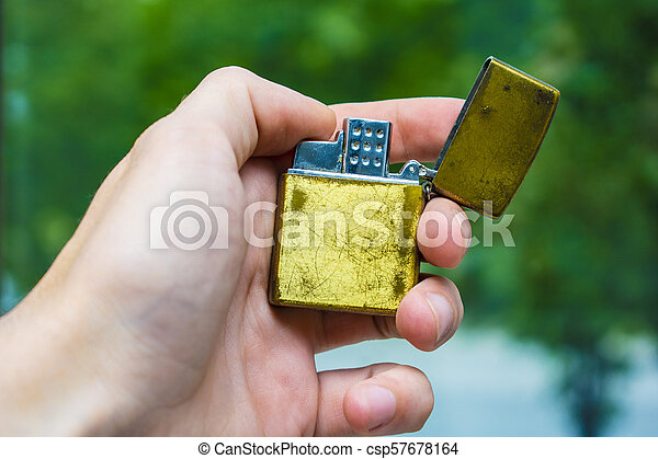 lighter of gold color in hand against the background of nature - csp57678164