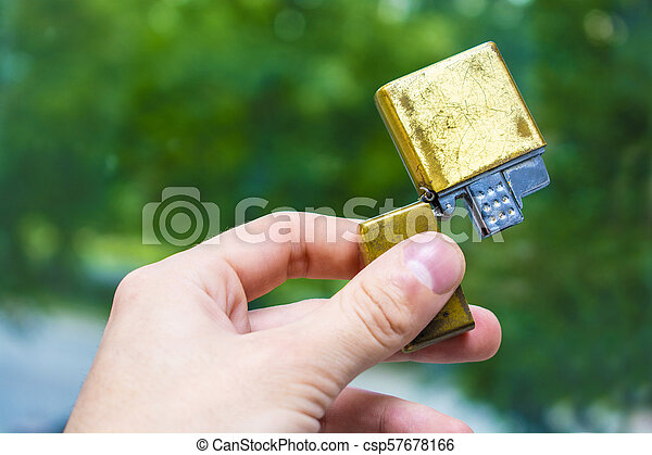 lighter of gold color in hand against the background of nature - csp57678166