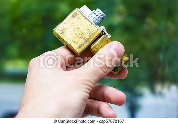 lighter of gold color in hand against the background of nature - csp57678167