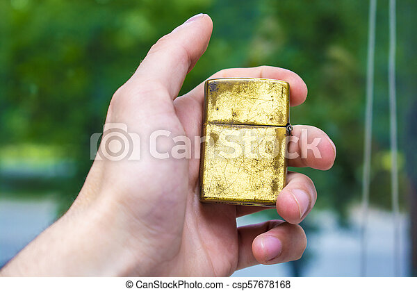 lighter of gold color in hand against the background of nature - csp57678168