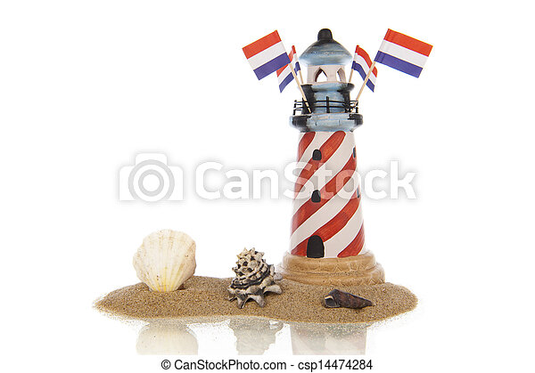 Lighthouse with flags and assorted shells in sand - csp14474284