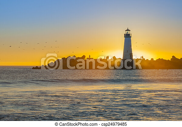 Lighthouse with light beam at sunset - csp24979485