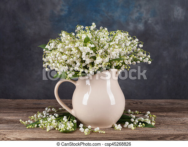 Lilies of the valley in vase on old board - csp45268826