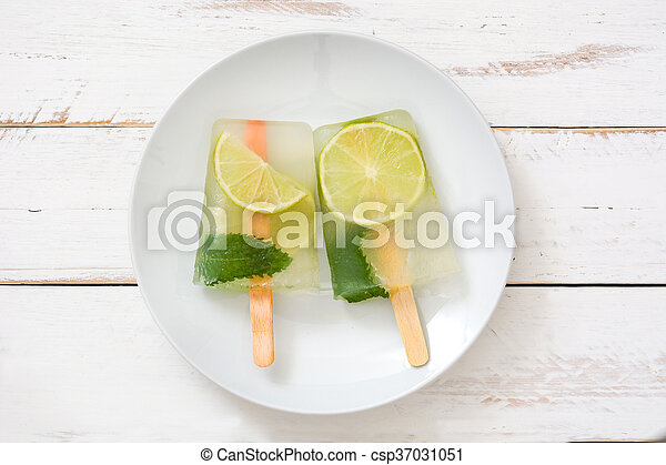 Lime popsicles on white wooden - csp37031051