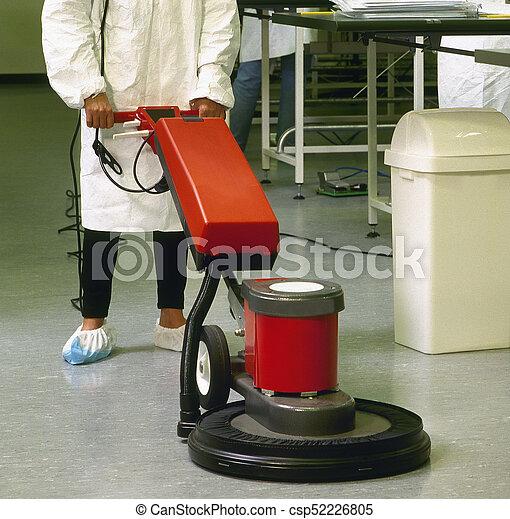 Una mujer de limpieza con uniforme limpiando pasillos - csp52226805
