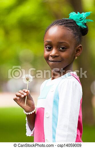 Retrato al aire libre de una joven y linda chica negra sosteniendo una flor de diente de león, gente africana - csp14059009