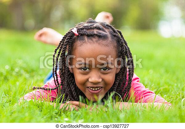 Retrato al aire libre de una joven y linda chica negra recostada en la hierba y sonriendo, gente africana - csp13927727