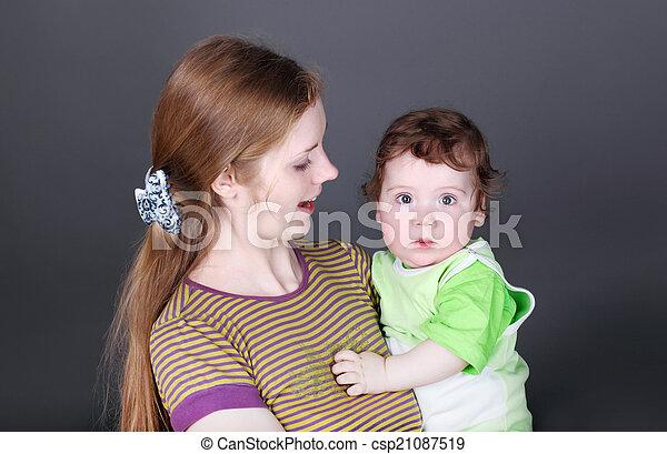 Retrato de madre joven y feliz con un bebé en sus brazos - csp21087519