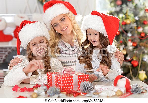 Retrato de feliz madre joven con sus dos lindas hijas celebrando la Navidad - csp62453243