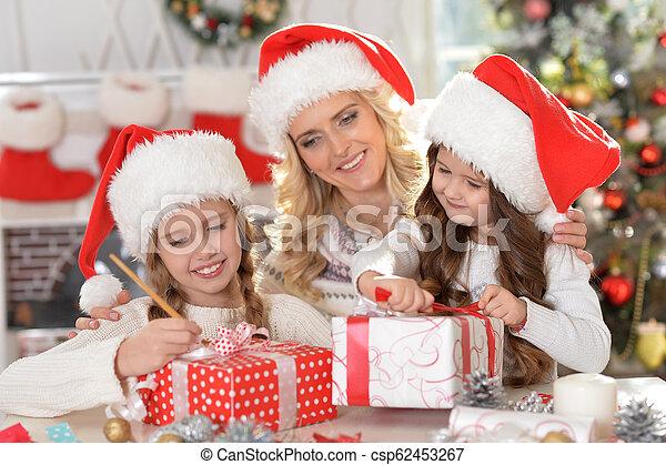 Retrato de feliz madre joven con sus dos lindas hijas celebrando la Navidad - csp62453267