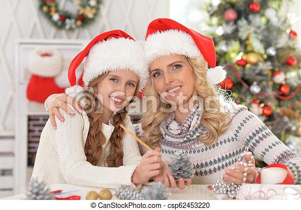 Retrato de lindas madres y su hija preparándose para Navidad - csp62453220